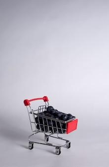 Carrello in metallo con mirtilli su uno sfondo bianco con una copia dello spazio. orientamento verticale