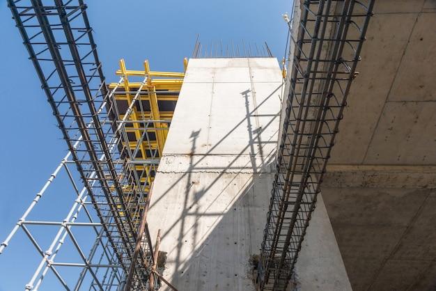 Strutture metalliche in calcestruzzo dell'edificio in costruzione. ponteggi e supporti