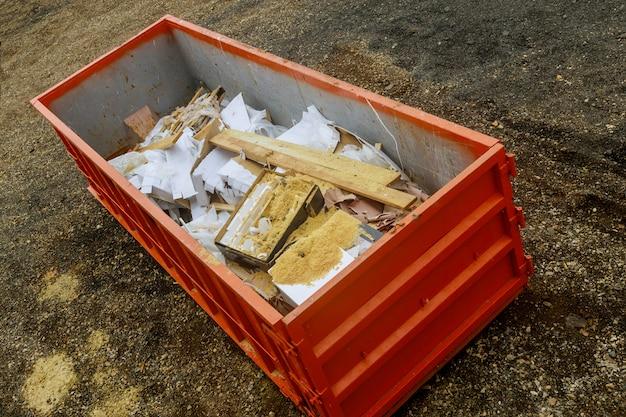 Bidoni della spazzatura dei rifiuti della costruzione del contenitore del metallo sul rinnovamento della casa.