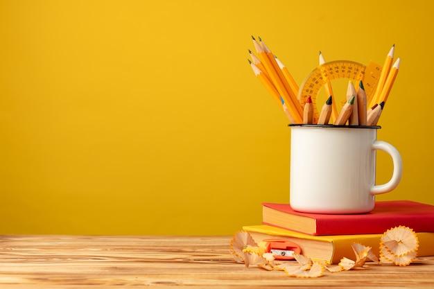 Tazza di metallo con matite taglienti e trucioli di matita sulla scrivania in legno su sfondo giallo