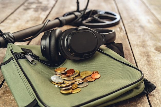 Metal detector, borsa e monete su tavola di legno da vicino
