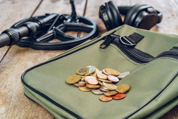 Metal detector e mazzo di monete sulla tavola di legno si chiuda