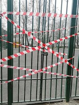 La porta di metallo si chiuse con una catena. la porta è legata con un nastro di contenimento. aree chiuse durante la quarantena. autoisolamento dal coronavirus