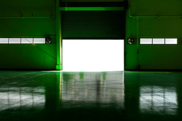 Porta della fabbrica di metallo e area verde del pavimento con la luce del sole.