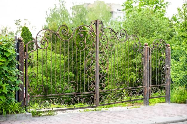 Cancelli forgiati in metallo con un cancello per le auto per entrare nel cortile e sicurezza