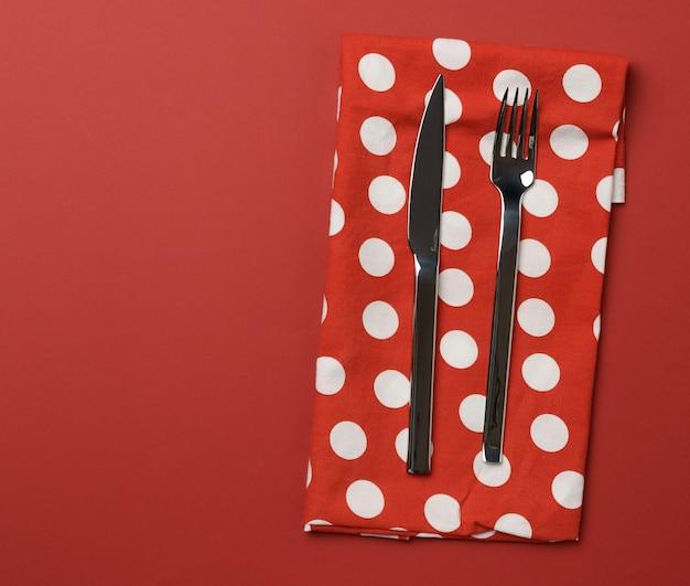 Forchetta e coltello in metallo, sfondo rosso, posto per un'iscrizione, vista dall'alto