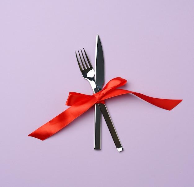 Forchetta e coltello in metallo legati con un nastro di seta rossa, sfondo viola, vista dall'alto