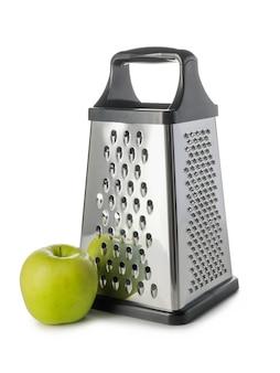 Grattugia e mela del metallo su fondo bianco