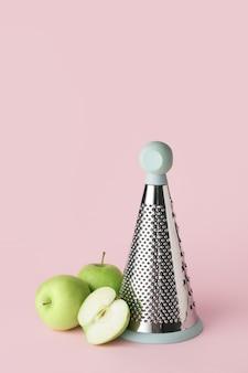 Grattugia in metallo e mele su sfondo colorato