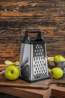 Grattugia in metallo e mele su fondo in legno
