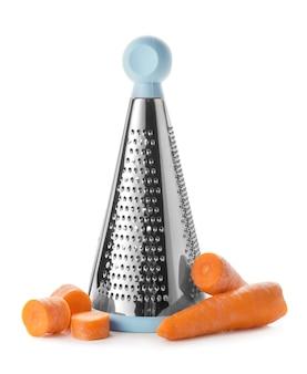 Grattugia in metallo e carote su sfondo bianco