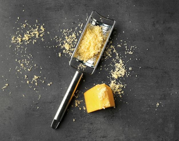 Grattugia e formaggio in metallo su sfondo scuro