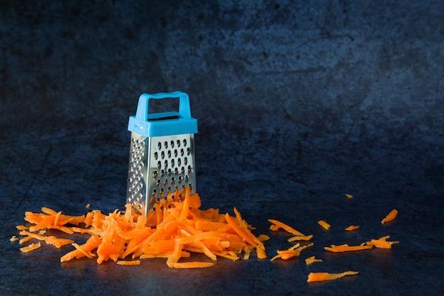 Una grattugia di metallo si trova su uno scivolo di carote grattugiate su uno sfondo blu scuro