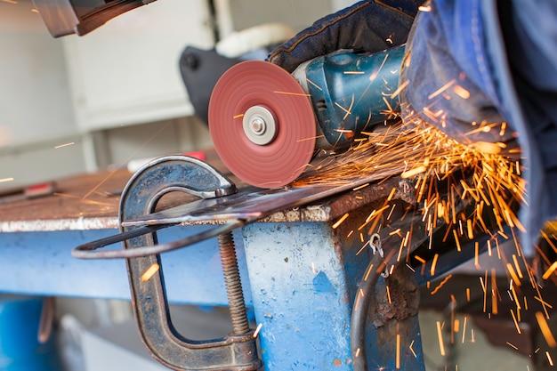 La molatura del metallo su piastra d'acciaio con flash di scintille si chiude indossando guanti protettivi