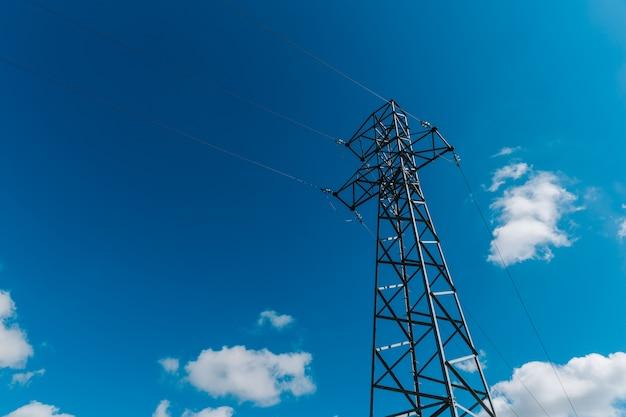 Torre ad alta tensione in metallo contro il cielo blu con nuvole bianche