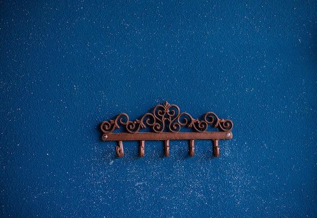Ganci metallici sullo sfondo di una parete blu. intonaco sul muro. superficie ruvida e irregolare.