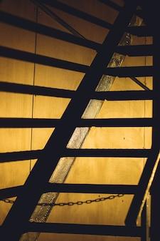 La scala in metallo crea lunghe linee d'ombra nere sul muro durante il tramonto.