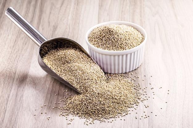 Cucchiaio dosatore in metallo con quinoa in grani. seme sano, cibo vegano