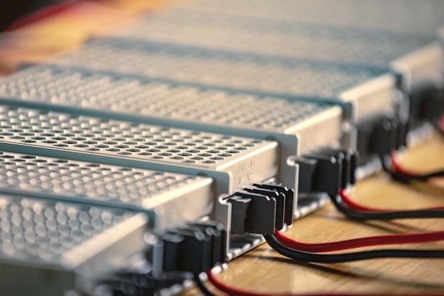 Le custodie in rete metallica di alimentazione e cavi sono su un tavolo di legno durante la produzione di computer ad alta tecnologia