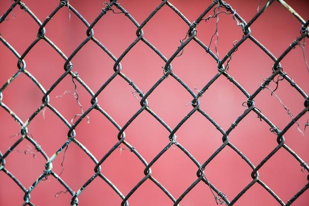 Primo piano della maglia metallica su uno spazio rosso