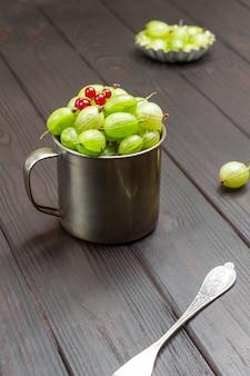 Tazza in metallo con uva spina verde e ribes rosso sulla parte superiore. fondo in legno scuro. vista dall'alto