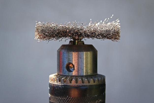 Spazzola con ugello in metallo per trapano elettrico per spazzolare il legno su sfondo grigio.
