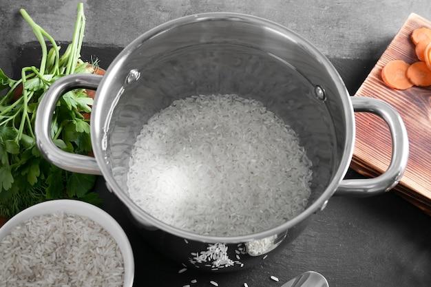 Padella in metallo con riso e altri prodotti sul primo piano della tavola