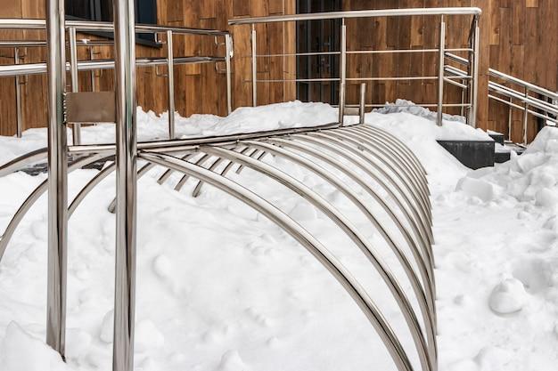 Parcheggio metallico per biciclette e scooter sulla neve all'ingresso dell'edificio