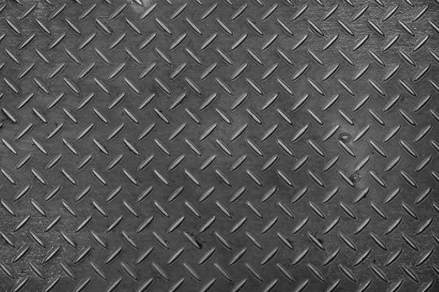 Piastra metallica strutturata con forme a rombo, sfondo di metallo sporco scuro o superficie in acciaio