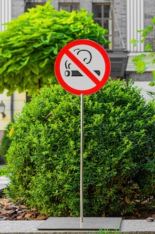 Palo di metallo con cartello per non fumatori in luogo pubblico.