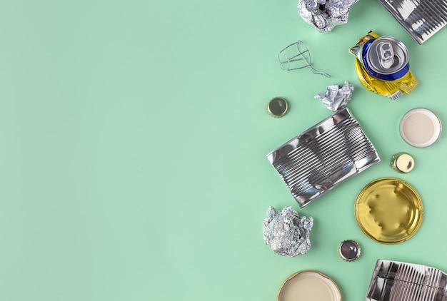 Metallo riciclabile, stagno e alluminio su uno sfondo verde