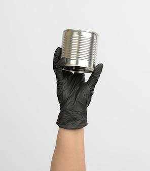 Barattolo di latta rotondo del metallo in una mano femminile su una priorità bassa bianca, fine in su