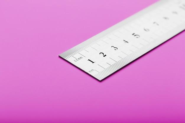 Righello di metallo sul primo piano rosa con una copia del posto per il testo.