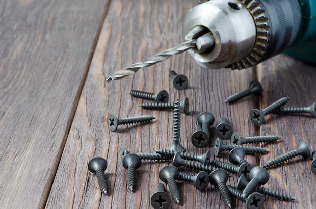 Viti metalliche e un trapano elettrico su un tavolo di legno. strumento per il fissaggio e la riparazione.