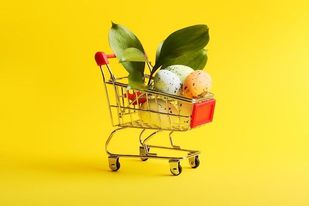 Cestino della spesa in metallo con vegetazione fresca e uova colorate in esso. concetto di pasqua. sfondo colorato e luminoso.