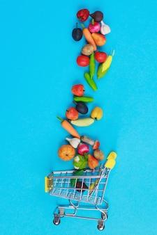 Carrello della spesa in metallo con frutta e verdura su sfondo blu. carrello della spesa in miniatura giocattolo