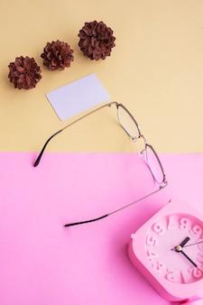 Occhiali quadrati in metallo nella foto in stile estivo minimale su sfondo rosa pastello e giallo. sveglia, fiori di pino, biglietti da visita