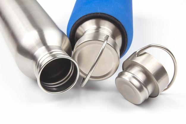 Boccette d'acqua in acciaio metallo su uno spazio bianco. utensili per bere in metallo