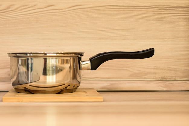 Casseruola di metallo in acciaio inossidabile sullo sfondo di una parete in legno beige e di un tavolo luminoso