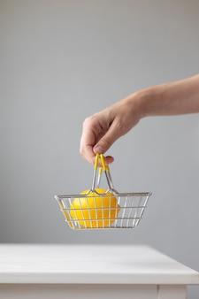 Cestino per alimenti in metallo per supermercati con banconote e monete al limone su un tabl bianco