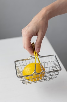 Cestino per alimenti in metallo per supermercati con banconote e monete al limone su un tavolo bianco