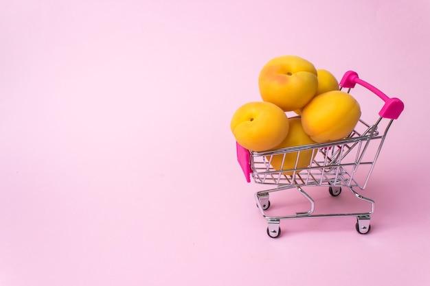 Un carrello per supermercati in metallo in miniatura con albicocche. shopping, acquisti, supermercato, saldi