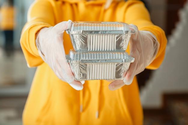 Contenitore per alimenti da asporto in metallo per la consegna di cibo da asporto donna in guanti lavora con ordini da asporto cameriere che dà pasto da asporto mentre blocco del coronavirus della città covid arresto