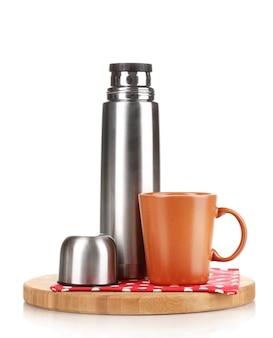 Thermos in metallo con tazza su tavola di legno isolato su bianco