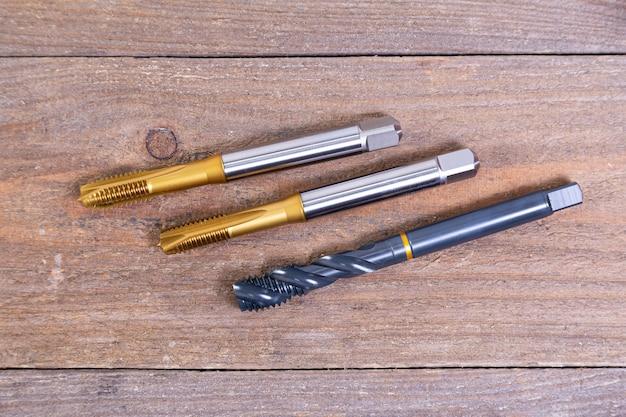 Maschi per filettatura in metallo. strumento per la lavorazione del metallo su una tavola di legno.