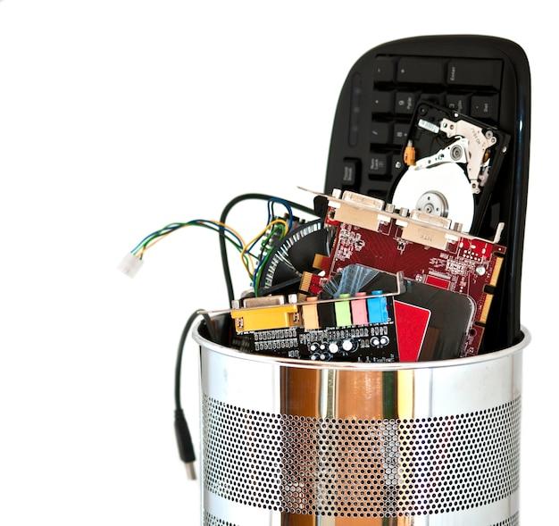 Pattumiera in metallo contenente rifiuti di computer isolati su sfondo bianco