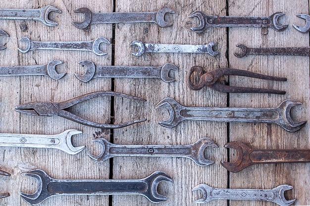 Strumenti arrugginiti della chiave del metallo che si trovano su una tavola di legno nera. martello, scalpello, seghetto, chiave in metallo.