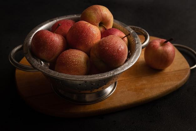 Ciotola metallica piena di mele mature rosse sul tagliere di legno ancora in vita. ingredienti per la torta di mele. cucinare a casa