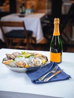 Ciotola metallica con ostriche e bottiglia di champagne