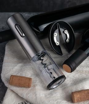 Cavatappi elettronico a batteria metallico. nelle vicinanze si trovano due bottiglie di vino e sughero. sfondo di legno e tessuto. avvicinamento